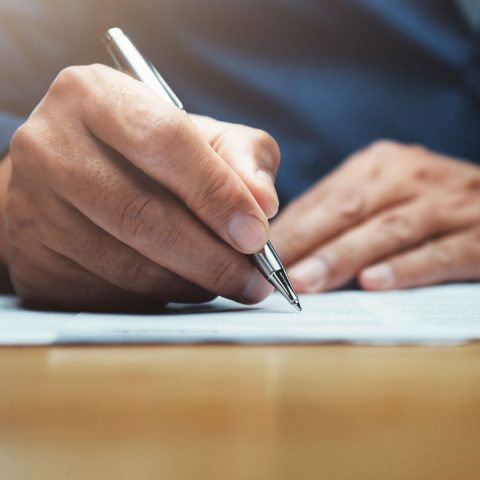 businessman writing on paper report in office